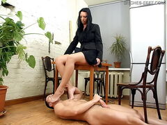 Anna's slave is lying at her feet and she's trying to finish her work with the computer. She orders her slave to start licking her feet. When she's no satisfied with how he works with his tongue she spits to his face or slaps him. Then she starts playing